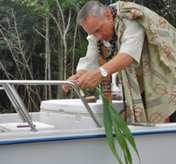 Tying sacred ti leaf to corners of boat